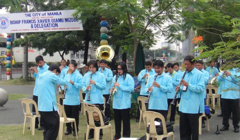 Manila barangay band serenading Japanese pilgrims with Filipino music.