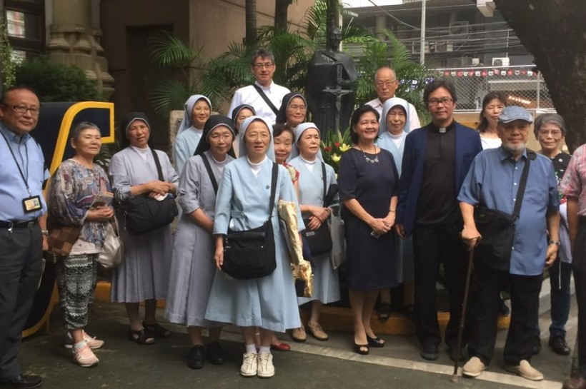 The Nagasaki group poses for memento photographs in front of the statue of Blessed Justo Takayama Ukon